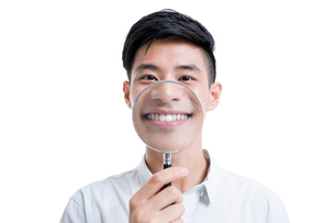 Young man holding a magnifying glass in front of his mouthの写真素材 [FYI02219461]