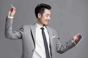 Happy young businessman using digital tabletの写真素材 [FYI02219559]