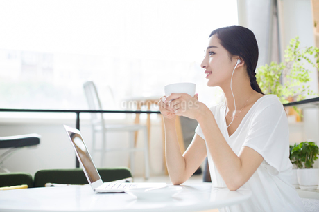 Happy young woman listening to music in coffee shopの写真素材 [FYI02219739]