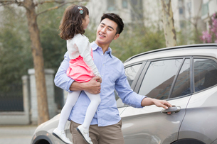 Happy father opening car door with daughter in his armsの写真素材 [FYI02219891]