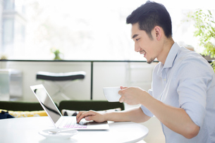 Happy young man using laptop in coffee shopの写真素材 [FYI02219944]