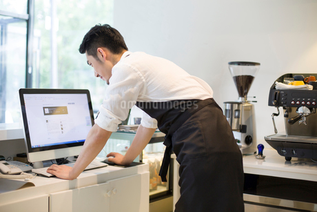 Coffee shop owner using computerの写真素材 [FYI02220045]