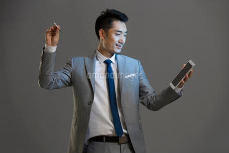 Happy young businessman using digital tabletの写真素材 [FYI02220077]