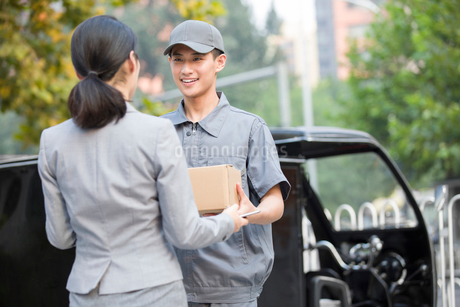 Young woman getting a package from delivery personの写真素材 [FYI02220700]