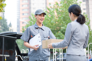 Young woman getting a package from delivery personの写真素材 [FYI02220705]