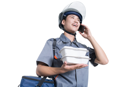 Take-out deliveryman talking on the phoneの写真素材 [FYI02220885]