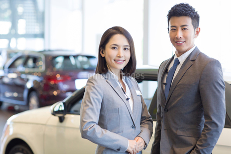 Confident salespeople standing with new cars in showroomの写真素材 [FYI02220955]