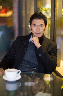 Young man drinking coffee in caf?の写真素材 [FYI02221059]
