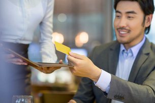 Chinese businessman paying bill by credit card in restaurantの写真素材 [FYI02221064]
