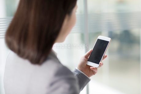 Young businesswoman using smart phoneの写真素材 [FYI02221126]