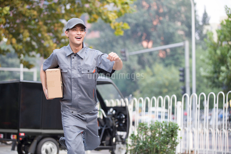 Delivery person delivering packageの写真素材 [FYI02221141]