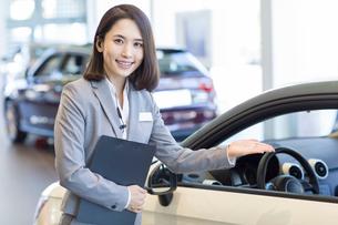 Confident saleswoman standing with new cars in showroomの写真素材 [FYI02221284]