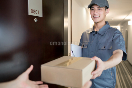 Delivery person holding packageの写真素材 [FYI02221413]