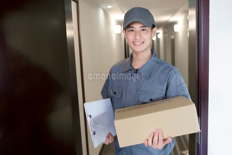 Delivery person holding packageの写真素材 [FYI02221615]