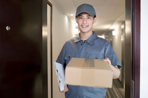 Delivery person holding packageの写真素材 [FYI02221647]
