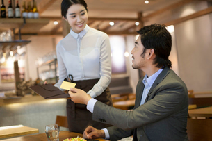 Chinese businessman paying bill by credit card in restaurantの写真素材 [FYI02221692]