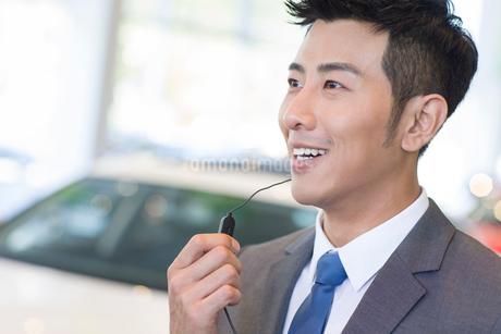 Confident car salesman with headsetの写真素材 [FYI02221916]
