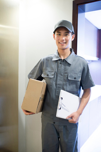 Delivery person holding packageの写真素材 [FYI02221932]