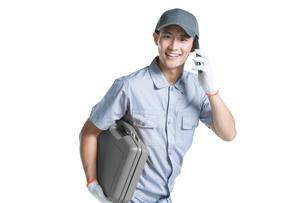 Repairman talking on the phoneの写真素材 [FYI02222008]