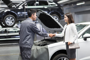 Auto mechanic and car owner shaking handsの写真素材 [FYI02222739]