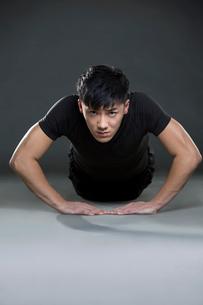 Young man doing push-upsの写真素材 [FYI02222806]