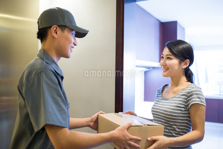 Young woman getting a package from delivery personの写真素材 [FYI02223090]