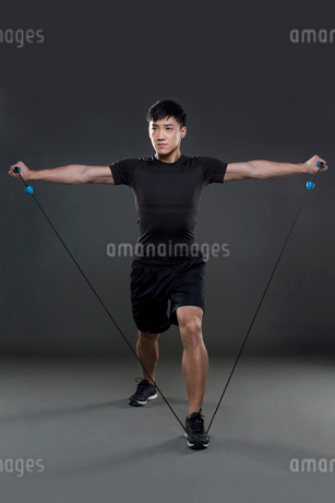 Young man exercising with resistance bandの写真素材 [FYI02223253]