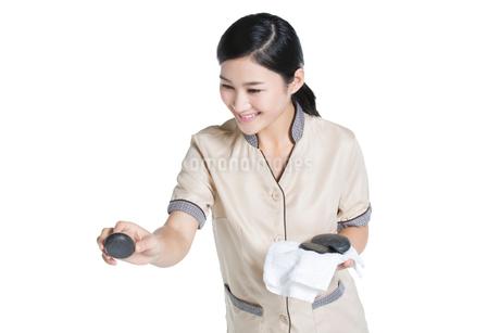 Massage therapist doing hot stone massageの写真素材 [FYI02223300]