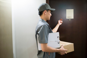 Delivery person delivering packageの写真素材 [FYI02223310]