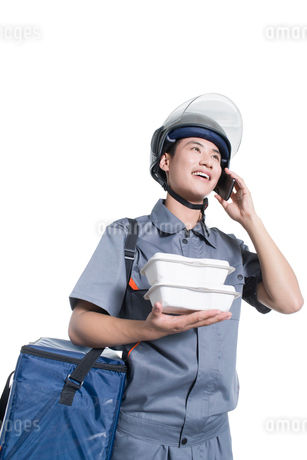Take-out deliveryman talking on the phoneの写真素材 [FYI02223427]