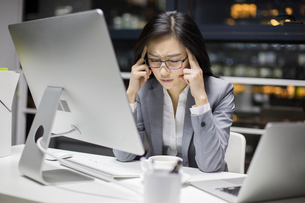 Businesswoman working late in officeの写真素材 [FYI02223498]