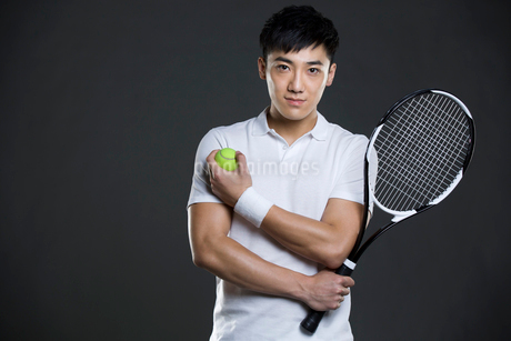 Young man holding tennis ball and racketの写真素材 [FYI02223595]