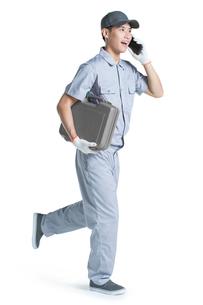 Repairman talking on the phoneの写真素材 [FYI02223606]