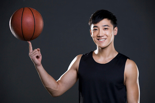 Young man spinning basketball on fingerの写真素材 [FYI02223635]