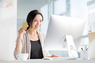 Young woman shopping online in officeの写真素材 [FYI02223668]