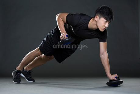 Young man doing push-upsの写真素材 [FYI02223717]