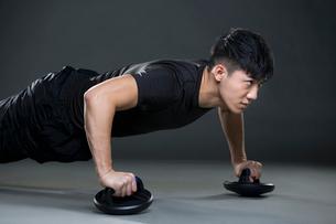 Young man doing push-upsの写真素材 [FYI02223731]