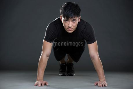 Young man doing push-upsの写真素材 [FYI02223761]