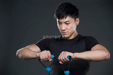 Young man exercising with resistance bandの写真素材 [FYI02223792]