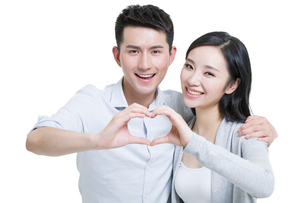 Happy young Chinese couple doing heart shape gestureの写真素材 [FYI02223972]