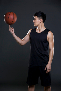 Young man spinning basketball on fingerの写真素材 [FYI02224009]