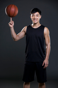 Young man spinning basketball on fingerの写真素材 [FYI02224034]