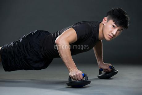 Young man doing push-upsの写真素材 [FYI02224052]