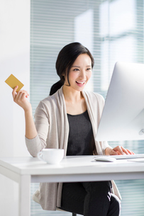Young woman shopping online in officeの写真素材 [FYI02224084]