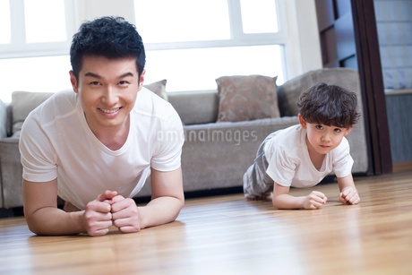 Young father and son exercising at homeの写真素材 [FYI02224093]
