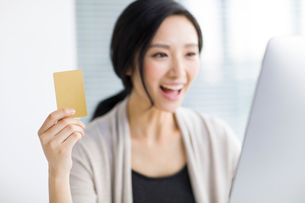 Young woman shopping online in officeの写真素材 [FYI02224184]