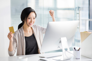 Young woman shopping online in officeの写真素材 [FYI02224192]