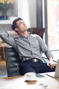 Tired young man relaxing in officeの写真素材 [FYI02224197]