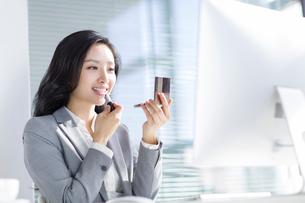 Businesswoman applying lipstick in officeの写真素材 [FYI02224246]