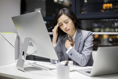 Businesswoman working late in officeの写真素材 [FYI02224247]